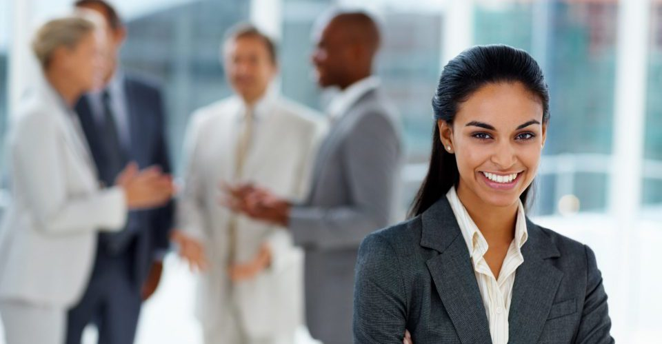 Businesswoman smiling with colleagues in the background